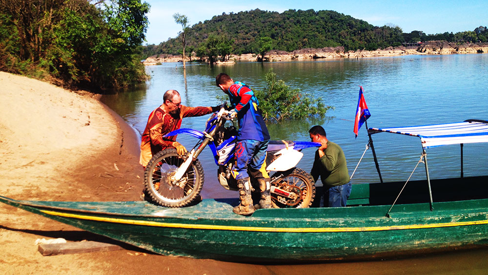 Loading a dirtbike onto a boat to cross the Mekong